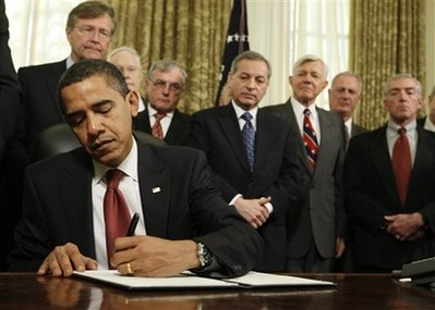 President Barack Obama signs a series of executive orders, including one closing of the prison at Guantanamo Bay, Thursday, Jan. 22, 2009, in the Oval Office of the White House in Washington. (AP Photo/Charles Dharapak)