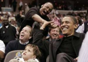 U.S. President Barack Obama, sitting next to 5-year old Nick Aiello (L), gets a high five from fan Miles Rawls at the Washington Wizards NBA basketball game against the Chicago Bulls in Washington February 27, 2009. Reuters/Molly Riley (United States)